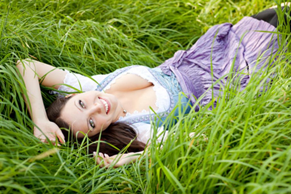 Junge Frau liegt in der Wiese am Rücken